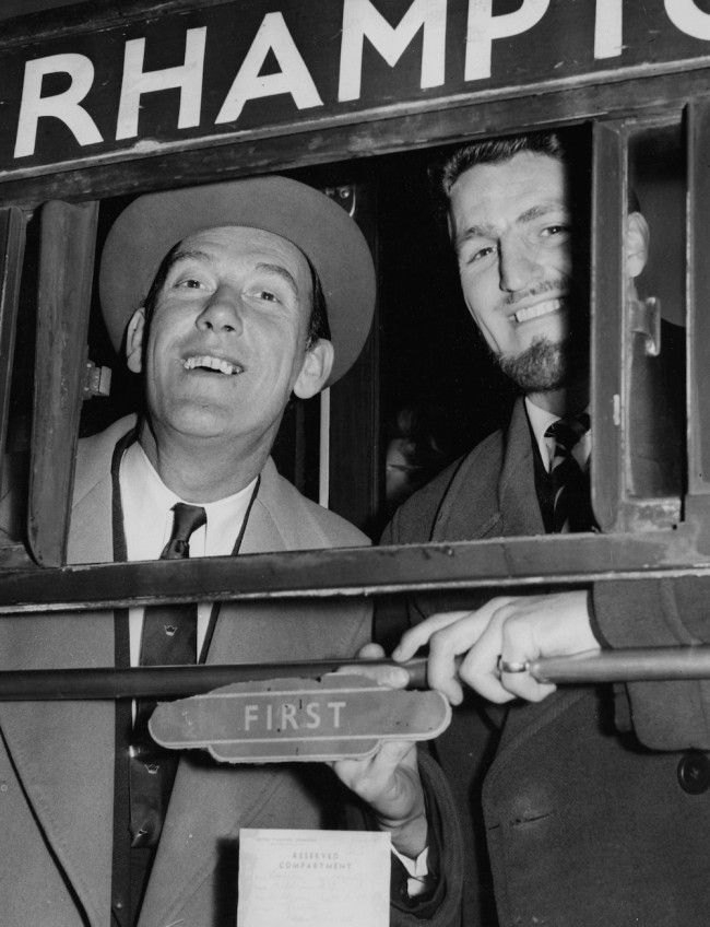 English comedian Tommy Trinder (left), Director of Fulham Football Club, and Fulham football player Jimmy Hill smiling out of their train carriage window as they head for Villa Park to play Manchester United for the FA Cup, at Euston Station, London, March 21st 1958. (Photo by John Franks/Keystone/Getty Images)
