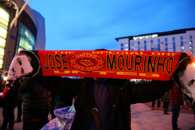 MANCHESTER, ENGLAND - DECEMBER 28: A fan poses with a Manchester United scarf displaying the image and name of former Chelsea manager Jose Mourinho, outside the stadium before the Barclays Premier League match between Manchester United and Chelsea at Old Trafford on December 28, 2015 in Manchester, England. (Photo by Alex Livesey/Getty Images)