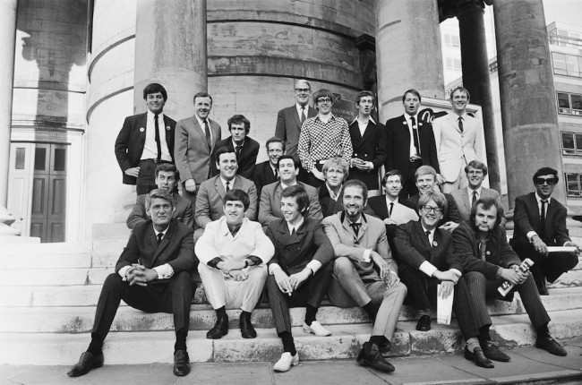 Radio One DJ's pose for a group photograph outside Broadcasting House after the BBC announce their new line up, London, 1967. Back row (left to right); Tony Blackburn, Jimmy Young, Kenny Everett, Duncan Johnson, Robin Scott (controller), David Ryder, Dave Cash, Pete Brady, David Symonds. Middle Row (left to right); Bob Holness, Terry Wogan, Barry Alldiss, Mike Lennox, Keith Skues, Chris Denning, Johnny Moran, Pete Myers. Front row (left to right); Pete Murray, Ed Stewart, Pete Drummond, Mike Raven, Mike Ahern, and John Peel. (Photo by Robert Stiggins/Express/Hulton Archive/Getty Images)