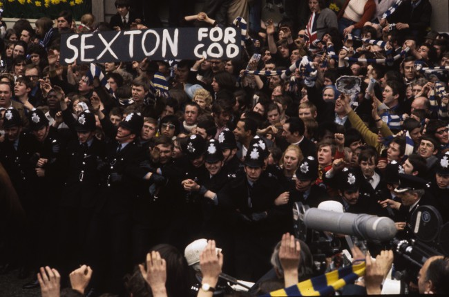 1970: Police keeping back crowds of Chelsea Football Club supporters as they strain for a glimpse of manager Dave Sexton. A banner in the crowd reads 'Sexton For God'. (Photo by A. Jones/Express/Getty Images)