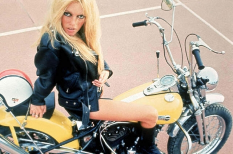 Brigitte Bardot posing on a yellow Harley-Davidson chopper built by Maurice Combalbert.