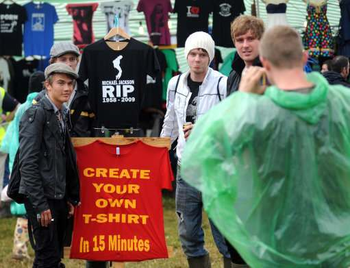 Festival goers pose for pictures beside a Michael Jackson tribute t-shirt during the 2009 Glastonbury Festival in Pilton, Somerset.