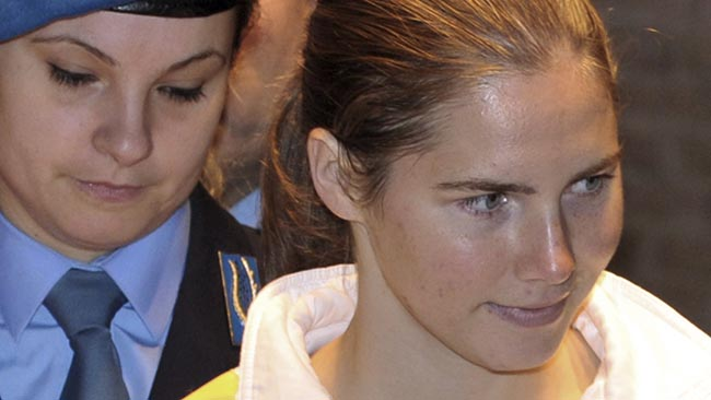 U.S. murder suspect Amanda Knox, right, is escorted by an Italian penitentiary police officer at a hearing in Perugia's court, Italy, Saturday, Nov. 28, 2009. Earlier this month, prosecutors requested life sentences for American student Knox and her former Italian boyfriend Raffaele Sollecito accused of killing a young British woman in Italy. Prosecutor Giuliano Mignini asked a jury in Perugia to convict Amanda Knox and Sollecito on charges of murder and sexual violence for their alleged role in the 2007 slaying of Meredith Kercher. They deny wrongdoing. (AP Photo/Stefano Medici)