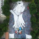 Artist paints sleeping giants on rooftops